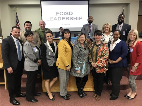 The assistant principals and executive directors of leadership standing at the front of the board room.