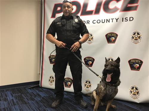 Officer Mesa and K-9 Officer Odin standing in front of the ECISD police banner.